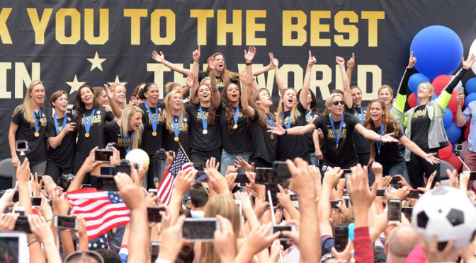 Members of the USWNT celebrate on stage during the ticker tape parade in their honor in New York City.