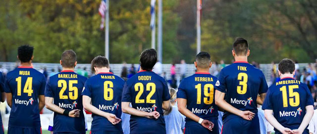 Saint Louis FC players stand for National Anthem