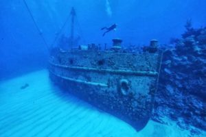 A diver swims near the wreckage of a sunken boat in the Bermuda Triangle